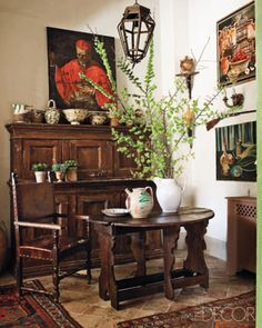 An Italian kitchen's cabinet and chair are 17th-century Tuscan, and the 16th-century table is from Umbria; the artwork includes an oil painting by designer and owner Antonello Radi, top right.