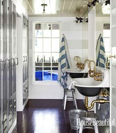 The bunk room bath is fitted with lockers for guests and family members. Dempster had the faucets on Kohler's Brockway sinks stripped down to the brass. The wall paneling is painted in alternating bands of flat and semigloss paint, echoing the stripe on the Pottery Barn towels.