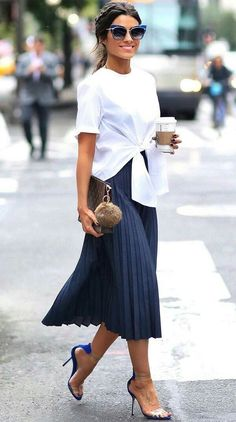 white shirt with tie front (styling), sun glasses and just a purse (minimal styling and accessories), no earrings (accessories), skirt length (silhouette), blue (color)