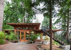"""Constructed from Douglas fir beams made from trees selected off the Coulson property, this post and beam studio doesn't fail to impress. The 42"""" overhangs carry run off from 900 square feet of sod roof, along recycled log boom chains, which trickle feed potted bamboo at the entrance. A salvaged curving iron staircase provides a"""