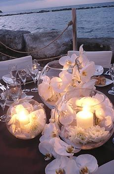 So beautiful and elegant- white flowers, candles in round glass bowls.