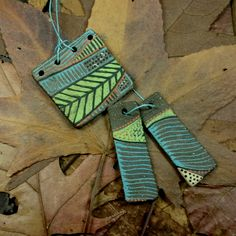 Three piece set of hand made and decorated ceramic clay stoneware jewelry components, side one.