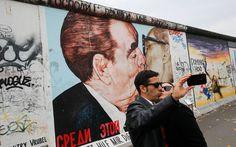 Casal de turistas tira foto em frente a uma pintura que mostra o ex-líder soviético Leonid Brezhnev beijando seu homólogo da Alemanha Oriental Erich Honecker na East Side Gallery, a maior parte remanescente do antigo Muro de Berlim, em novembro de 2014