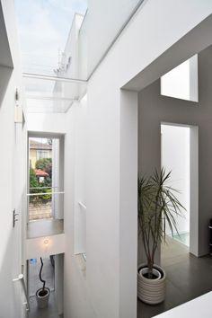階段を上がった部分から家の表側を見る。表の壁から天窓を経て裏の壁へと開口が続く。