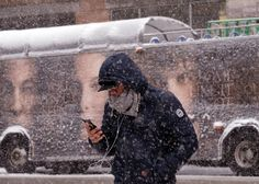A man uses his smartphone as he crosses a street during a winter storm in New York on March 5, 2015.