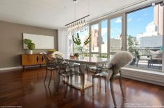 This NYC penthouse has warm wood flooring, a mid-century modern console table, clear plastic chairs, a hanging light fixture and a wall of glass that opens onto a patio.