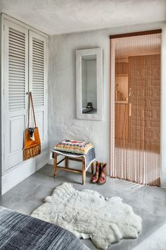Love the sheepskin rug and the simple details. Low stool/table. Decorative inlet. Striped bedcovers. Calm.