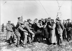 1915 German soldiers help a high-altitude observer remove his heavy clothes.