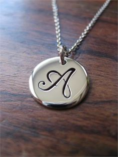 A handmade, silver initial pendant, made using argentium silver.   Please let me know on checkout if youd like a different letter. The pendant itself is approximately 1.5cm across and 1.2mm thick. It will come on an 18 Sterling silver chain, if youd like a 16 or 20 chain please leave a note during purchase.   If youd like a chain longer than 20 please message me before buying so that I can adjust the cost.   PLEASE NOTE - I typically make these designs once the order has taken place, so if…