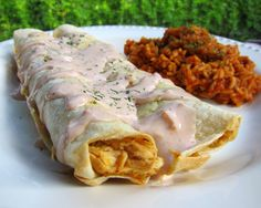 Chicken Ranch Enchiladas and Rice {Slow Cooker} Recipe - chicken slow cooked in taco seasoning, ranch mix, chicken broth. Top tortillas with cooked chicken, cheese, salsa and Ranch and bake for 20 minutes. Use leftover juices in crockpot to make super flavorful rice to go with the enchiladas! SO good. Better than the Mexican restaurant!