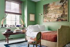 The walls of the master bedroom are painted in a custom-blended Benjamin Moore green and graced by a 19th-century French wallpaper pane