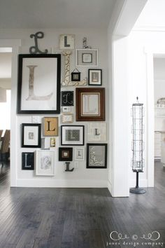 Emily from JDC's Wall of L's. Love this idea for a gallery wall theme! And super love the white walls and greyed down hardwood flooring.