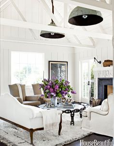 """Beach House Chic In a Marin County, California, beach house designed by Erin Martin and homeowner Kim Dempster, thirty-inch buoy lights, from Erin Martin Design, hang from ropes. """"The ceiling is high and narrow, and the lights bring it down and create a kind of canopy,"""" Martin says. """"It's like putting a hat on the space."""" A pair of antique French chairs are upholstered in natural linen."""