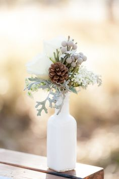Winter trend: use of texture. Pretty winter arrangement with pine cones, baby's breath and other greenery.