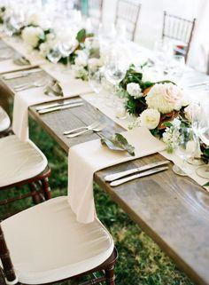 Como decorar una mesa larga: un camino central con guirnalda de flores y el detalle de una hoja sobre la servilleta del comensal. Fotografía: Austin Gros