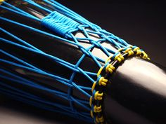Ashiko hand drum closeup, blue and yellow polyester rope.