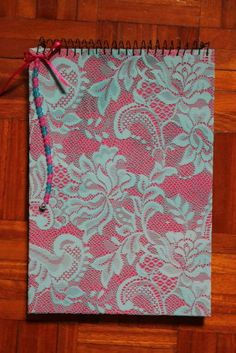 Caderno de capa dura, tipo bloco, encadernado com espiral, com 95 folhas brancas. Dimensões: 32 cm de comprimento por 21 cm de largura. Renda pintada à mão. Forrado, com cartolina rosa e ren...