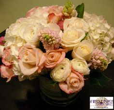 Soft whites and blush tones with hydrangea, roses, hyacinth, and other seasonal flowers in a low, lush centerpiece.