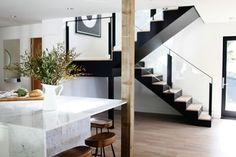 New glass and steel lookalike stair in a remodeled Ralph Anderson 1966 home in Bellevue, Washington, by interior designer Lisa Staton and builders Lochwood-Lozier, photo by Belathée   Remodelista