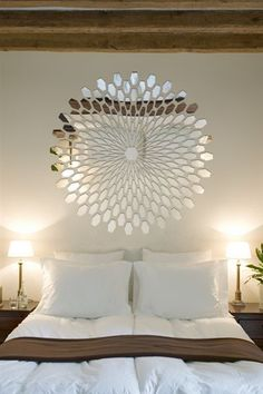 This mirrored collage is a unique way to create a piece of wall art, particularly effective above a headboard in a bedroom.