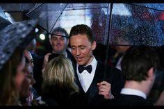 Tom Hiddleston does Gene Kelly with a transparent umbrella