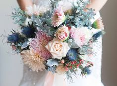Bridal bouquet in blush, ivory and grey with blue hints. Wedding bouquet of ivory roses, blush dahlias, blush spray roses, dusty blue thistle, acacia greenery and pink wax flowers. Bouquet made in garden free style.