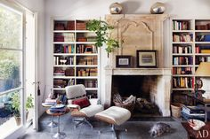 In the library, an Eames lounge chair and ottoman by Herman Miller sit next to a 17th-century French chimneypiece; the side tables are vintage. The family dog, Pepe, naps on a floor paved in Noir Belge marble.