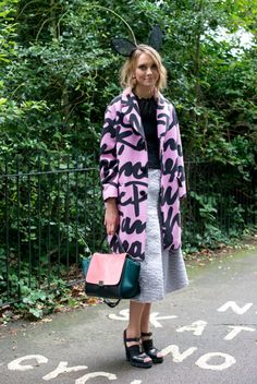 : This showgoer didn't shy away from statement-making pieces, opting for bunny ears, a graffiti-printed coat, and a bright, colorblock Céline bag.