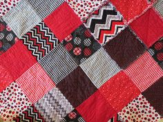 This reversible rag quilt is a perfect size for a crib, toddler or even as a lap quilt! The colors include red, black and grey. Patterns are modern and whimsy. Approximate Size: 47 x 59  Our quilts are washed and dried at least 4 times, so when it arrives it will be immediately ready for snuggling! Mojo quilts are reversible. One side is fuzzy and the other is more formal looking! NOTE: All Mojo Fabrics products are made in pet and smoke free homes. Care: wash warm, dry medium.  Our Shop…