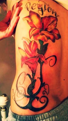 My first tattoo tiger lilies with my daughter's name at the top  #tattoo's, #flower tattoo's, #girl tattoo's, #tattoos, #flower tattoos, #girl tattoos