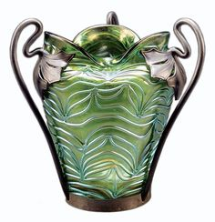 The pewter mounting with the mark of the Van Houten company helps identify this iridescent glass vase. Loetz and Kralik both used Van Houten pewter after 1890. Because of its quality, it auctioned for $854.