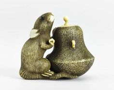 Netsuke of carved ivory, a rat sitting with its left forepaw on a tea-kettle, unsigned: Japan