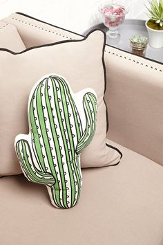 A canvas pillow with a cactus cutout design and striped pattern.