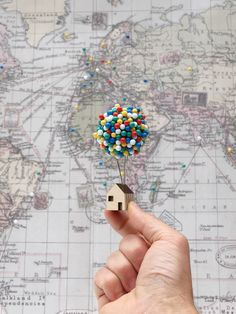 This fun new pin cushion by UK designer Clive Roddy promises to elevate your pushpin storage in a manner reminiscent of the Pixar film Up. The tiny wooden house with a large cork sphere can sit on a desk or mount to a cork-board or wall for easy storage. Currently available in his online shop.