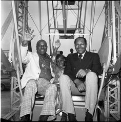 Mayor Tom Bradley sits with 9 year old Melody Reid on a Ferris wheel at the grand opening of the I-15 Shopping Center in Watts. Ted Watkins (right), head of the Watts Labor Community Action Committee that sponsored the event is sitting with Bradley and Reid. Harry Adams Collection. Institute for Arts and Media Photographs.