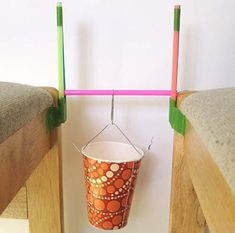A beam bridge made of straws with a load tester (cup) attached.
