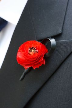 A single red ranunculus, tied with a black ribbon, makes a graphic statement against a black tux.