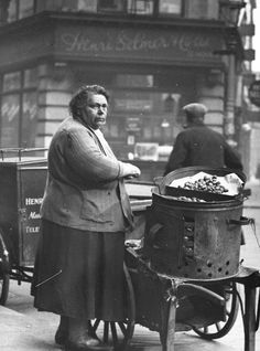 A miserable looking woman selling hot chestnuts in a Soho street, 1935.