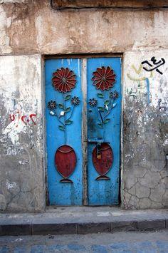 Puerta en Saná, Yemen. Se pueden ver algunas puertas antiguas que están hechos de madera y muy intrincada. Hoy en día se hacen puertas de metal con coloridos detalles que sont également muy interesante. Las puertas son una gran parte de la vida de Yemen