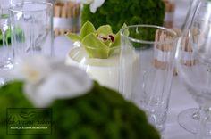 """Biało zielone dekoracje stołu weselnego w całości wykonane przez Agencję Ślubną Sroczyńskich """"Ślub Ręcznie Robiony"""". Świeże, wiosenne, z elementami stylu eko. Zielone świece w drewnianych świecznikach. Dekoracje kwiatowe, to kule z zielonych chryzantem, na których przysiadły niczym motylki białe storczyki. Zielone storczyki natomiast pływają w mleku w małych, kulistych wazonach."""