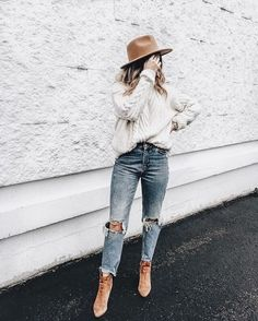casual winter bohemian style - chunky cable knit sweater, ripped jeans and neutral hat and booties