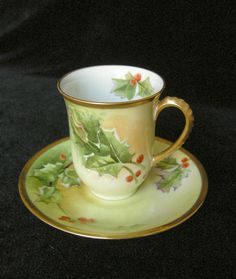 """STUNNING antique Limoges porcelain chocolate cup and saucer set with festive HOLLY.   There is raised hand painted enameling added to the leaves for artist dimension.    Both pieces are signed by the factory approved artist, """"Mary"""".       The edges and handles are heavily gilded. The gilding shows almost no wear.       It is double marked (more valuable) with the Lanternier Limoges France Mark 4 and the Limoges France Mark 1. The Marks date it to 1890."""
