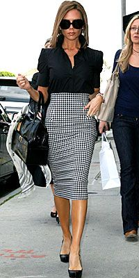 Victoria Beckham in black and white pencil skirt with black shirt.