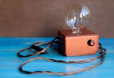 Modern Handmade Copper design table lamp with Edison bulb and dimmer  ∞∞∞ FREE SHIPPING to Europe ∞∞∞  Limited Edition, 1 copy  Copper painted MDF box Size - 10 x 10 x 6,5 cm. Light bulb Edison filament included 60w, E27 socket an dimmer Different 60 W Edison bulbs available.  You can deem light of bulb from barely noticeable to reeding light. Textile (Golden brown) 2meters cable with EU 2 pin plug Security: this lamp includes a dimmer and is not compatible with the eco (with tube) bulbs or…