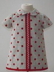 Vestido para bebe niña en paño gris con lunares en terciopelo rojo adornado con plisado rojo. Forrado.