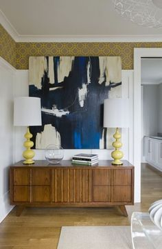 I like the way this is styled. These are my favorite colors, and I love the midcentury credenza. The wallpaper above the picture rail is a nice touch.