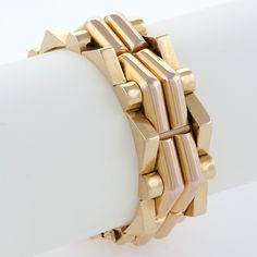 French 18 karat 'Tank Track' Yellow Gold Retro Bracelet  A French Retro 'Tank Track' 18 karat gold bracelet. The yellow gold bracelet is composed of outer triangular and circular elements edging center double curved triangular sections. 1940s