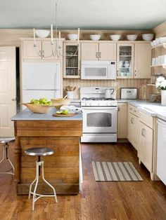 Try a Few Clever Tricks-A repurposed cast-off hardware-store counter serves as an island. Exposed shelves offer a convenient display opportunity and keep the room from feeling confined. Spray paint transformed a black fixture into a gleaming pendant.    Read more: Kitchen Island Ideas - Pictures of Kitchen Island Design - Country Living