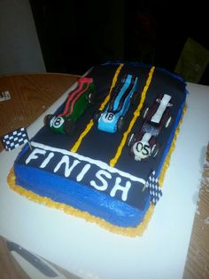 Pinewood derby cake for cub scout Blue & Gold banquet. Cars made from melted vanilla candies with mini oreos for the wheels, airheads candies for the detail work.