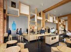 A display system made of stacked and suspended wooden boxes forms a signature feature in this new Blue Bottle cafe, which occupies part of a 1920s brick building in downtown San Francisco. Situated in the city's South of Market district, the cafe sits within a nearly century-old brick structure that once housed a Kohler plumbing supply warehouse. The coffeeshop occupies a storefront space that..